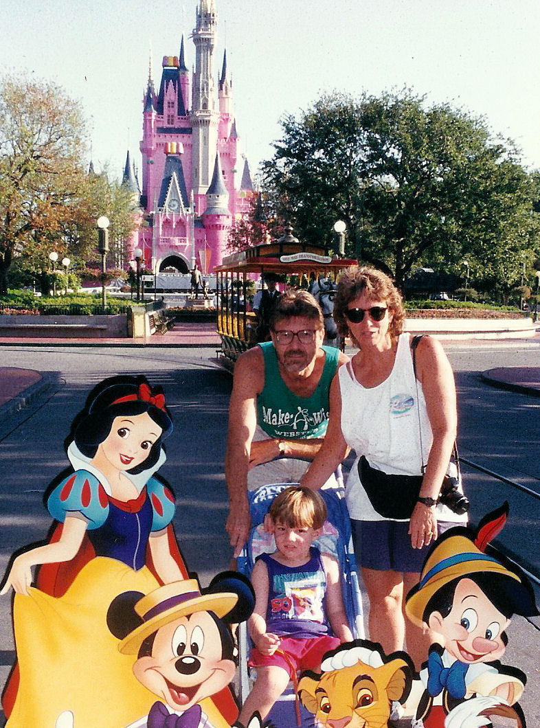 My parents and I with Disney characters in front of the then pink Cinderella Castle.