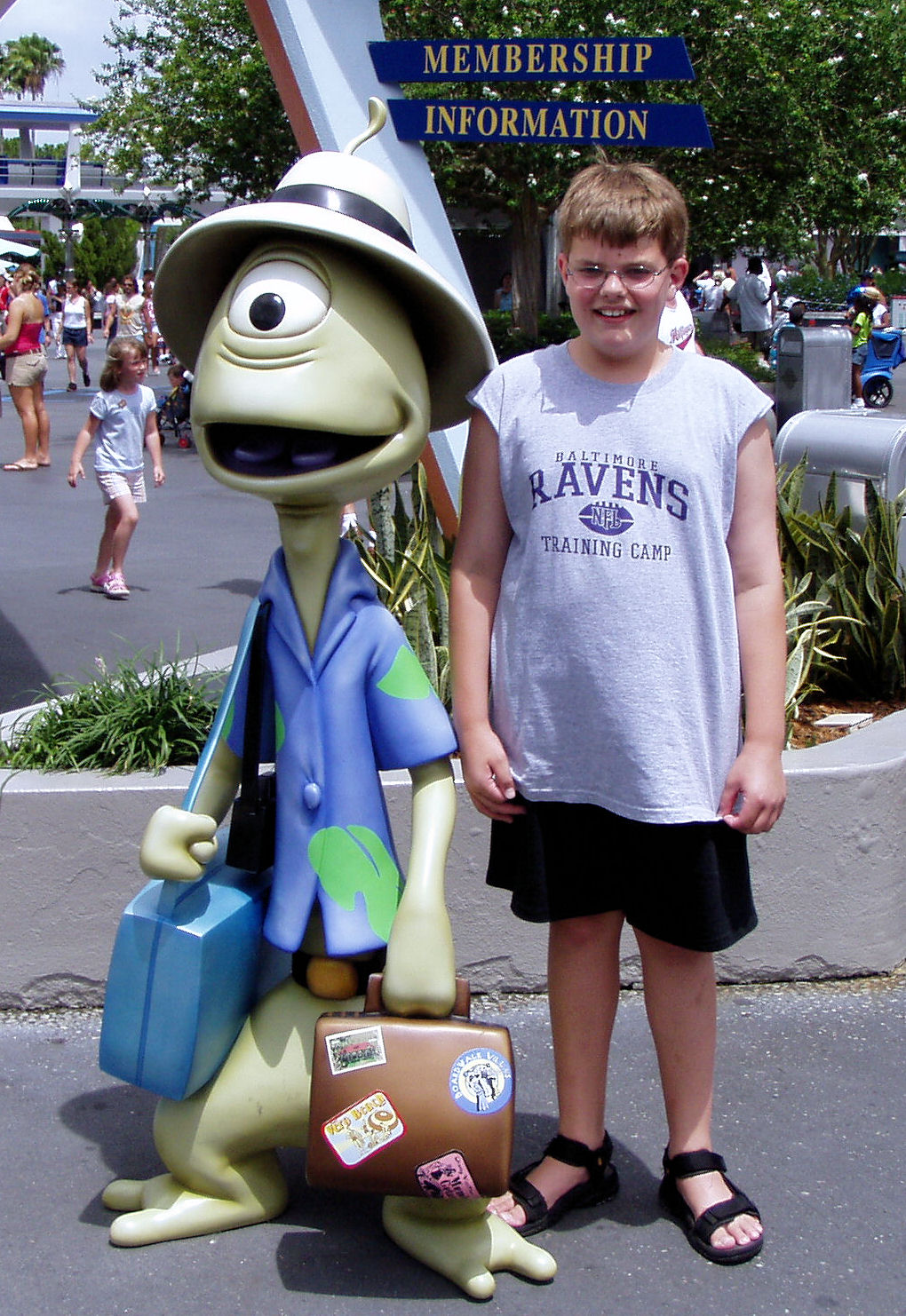 Me standing next to Pleakley by a kiosk for the Disney Vacation Club in The Magic Kingdom at Disney World.
